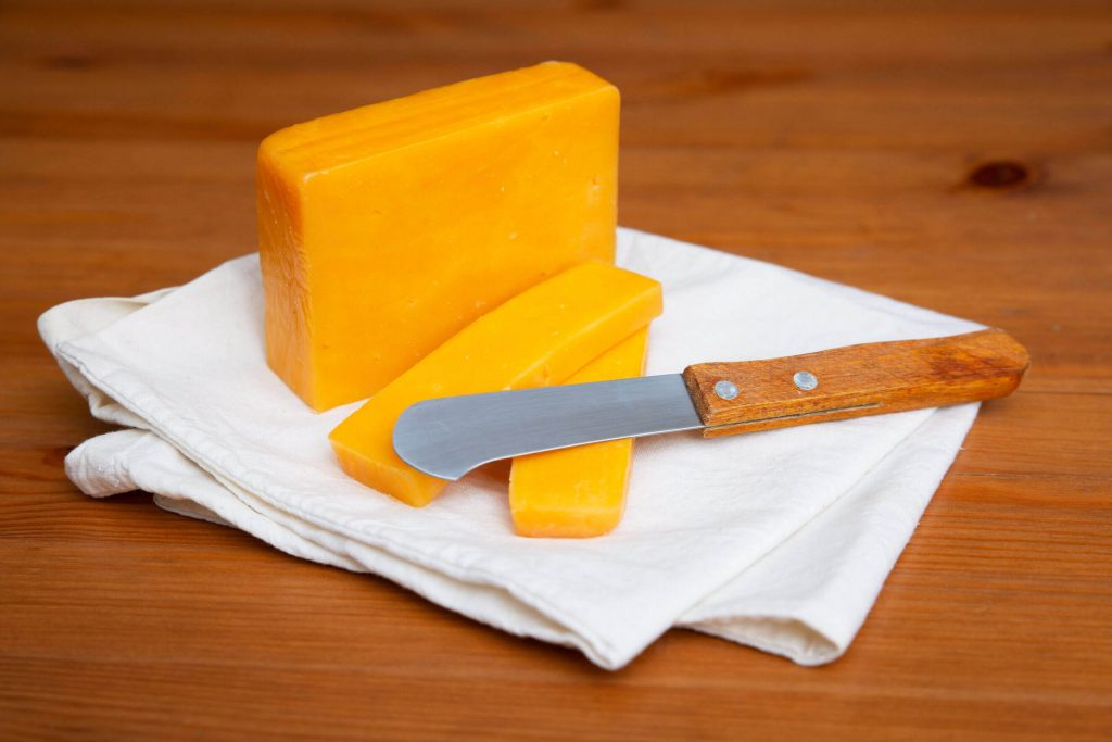 Queijo cheddar em um pano branco, cortado com uma faca de queijo.